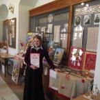 Обладательница диплома победителя на фоне выставки работ участников конкурса